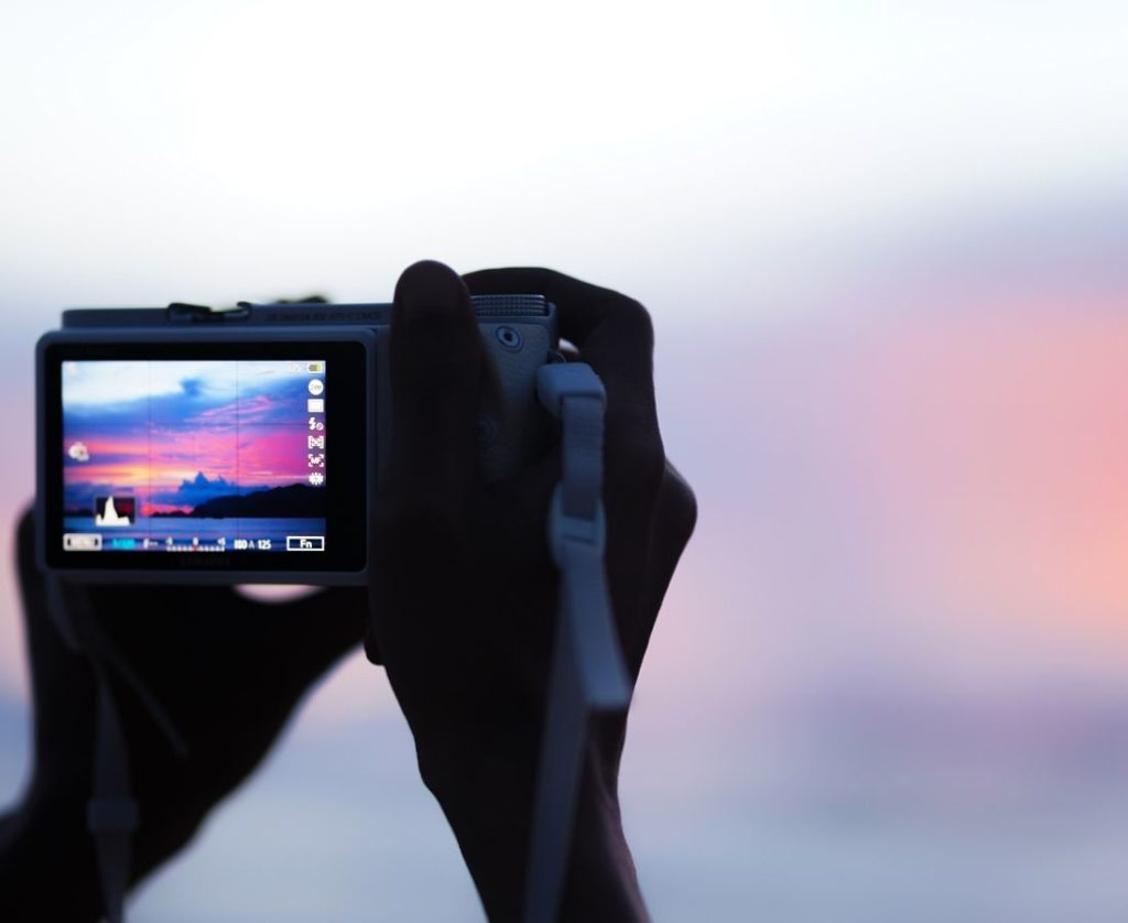 A man holding a camera having a screen protector on digital screen of camera